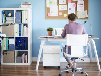 Ein junger Mann sitzt am Schreibtisch im Home Office