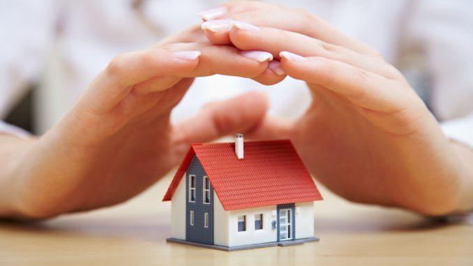 Jemand hält seine Hände über ein Haus