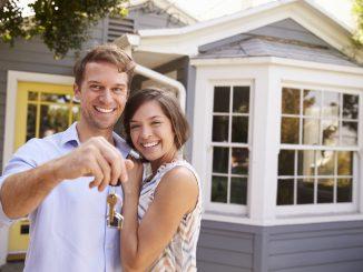Ein Paar steht vor einem Haus und hält einen Schlüssel in der Hand