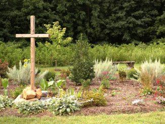 Ein Holzkreuz steht im Garten
