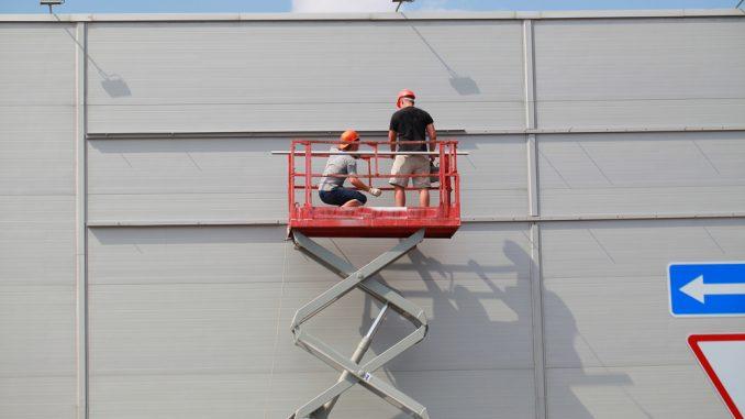 Zwei Männer stehen auf einer roten Arbeitsbühne, die hoch ausgefahren ist.