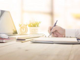 Jemand schreibt am Schreibtisch mit dem Kugelschreiber auf einem Notizblock