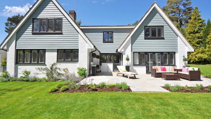 Ein weißes Haus mit grünem Garten