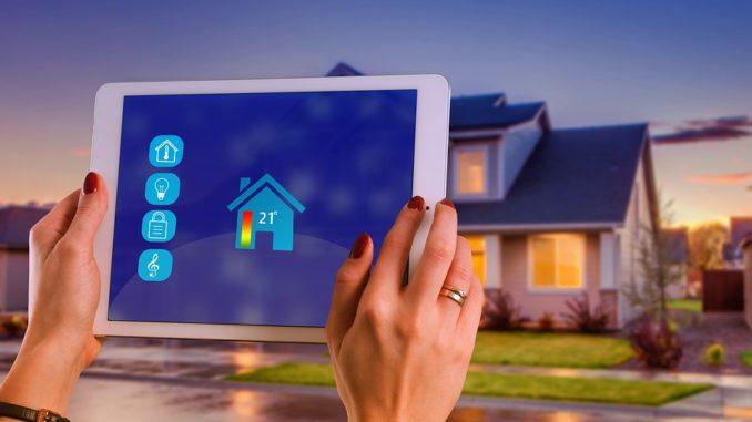 Smart Home Tablet und im Hintergrund steht ein Haus