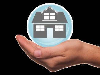Eine Hand trägt ein Haus bzw. ein Gebäude in blauer Blase