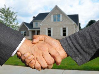 Vor einem Haus geben sich zwei Geschäftsleute die Hand.