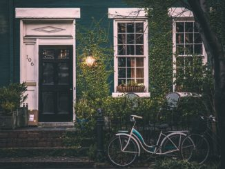 Ein altes grünes Haus vor dem ein Fahrrad steht