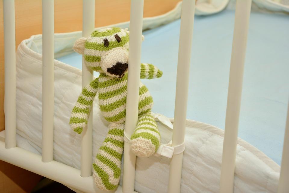 Grün gestreiftes Stofftier am Babybett