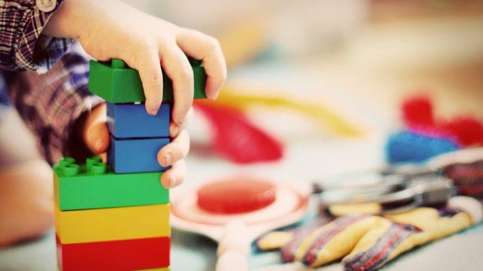 Ein kleines Kind setzt bunte Bauklötze aufeinander.