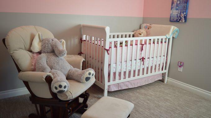 Kinderzimmer mit Babybett und einem großen Stofftier