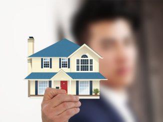 Ein Immobilienmakler hält ein Haus in der Hand