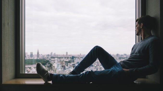 Mann sitzt alleine am Fenster.