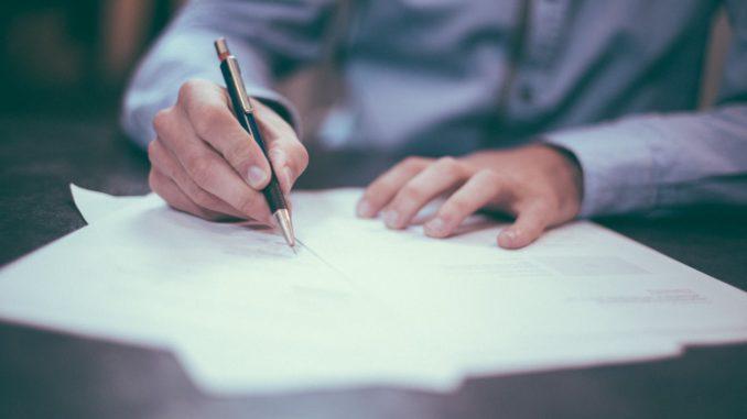 Ein Mann schreibt mit einem Kugelschreiber auf einem weißen Zettel