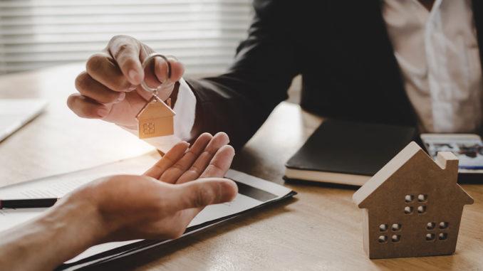Ein Immobilienmakler übergibt die Schlüssel