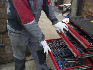 Mechaniker mit weißen Handschuhen öffnet Werkzeugwagen