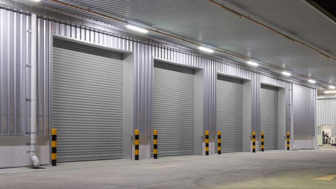 Fensterladen- oder Rolltor- und Betonboden außerhalb des Fabrikgebäudes für industriellen Hintergrund.