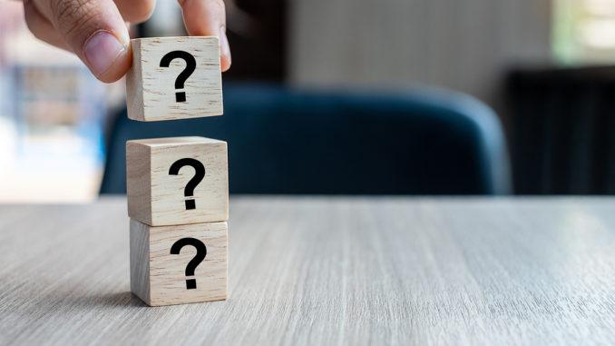 Drei Würfel gestapelt auf Tisch mit Fragezeichen darauf