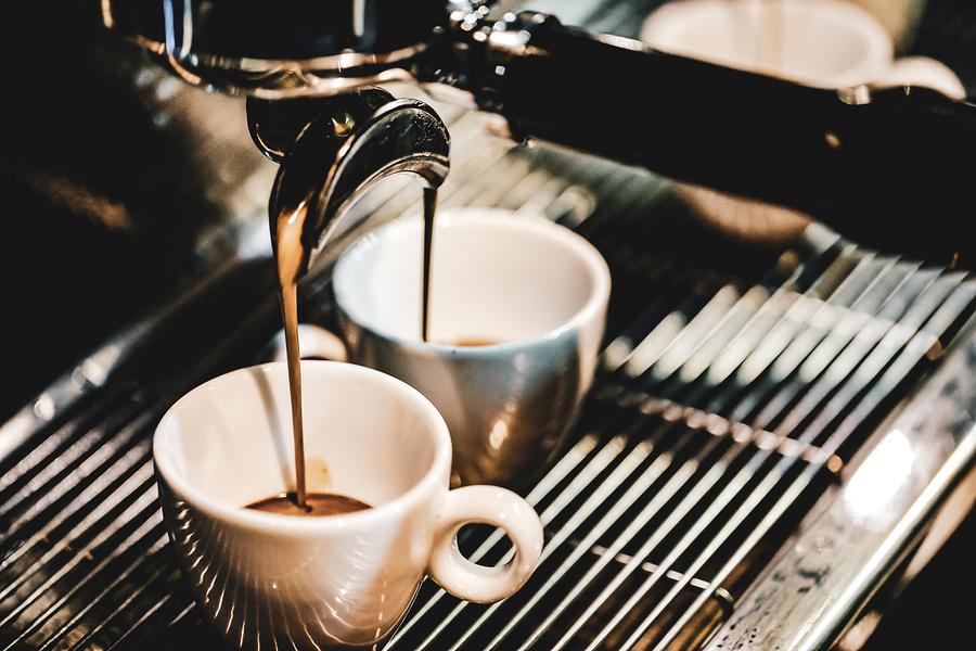 Zwei Tassen stehen unter Espressomaschine und werden befüllt