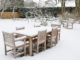 Gartenmöbel stehen von Schnee bedeckt im Garten