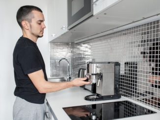 Mann bedient Kaffeevollautomat zuhause