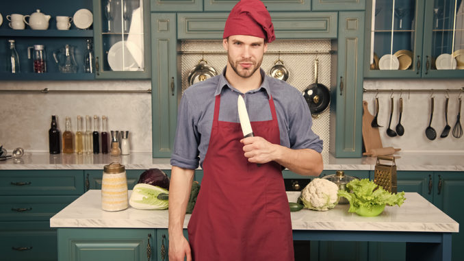Mannkoch tragen Schürze, die in der Küche kocht. Mann verwenden scharfes Keramikmesser. Scharfes Messer professionelles Werkzeug. Chefkoch wählen professionelle Werkzeuge. Küchenutensilien und Werkzeuge. Chef halten Messer Werkzeug bereit zu kochen.