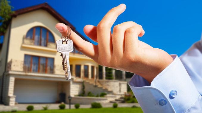 Ausgestreckte Hand hält Schlüssel mit Zeigefinger vor einem Luxushaus