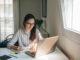 Hübsche Studentin mit Brille sitzt am Laptop.