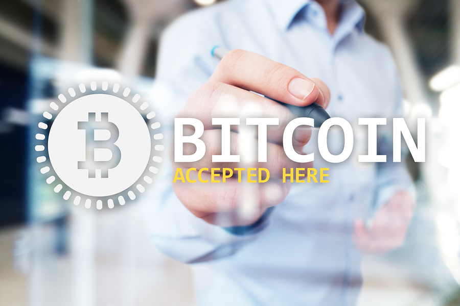 Mann im Hemd und Grafik davor mit bitcoin accepted here