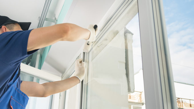 Ein Spezialist für die Installation von Kunststofffenstern beendet die Arbeit, indem er zusätzliche Geräte an das Fenster schraubt