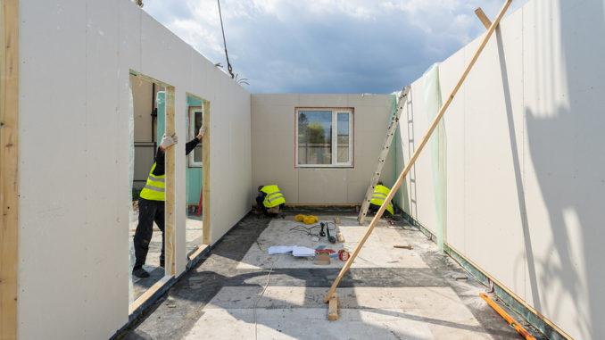 Bauprozess neues und modernes modulares Haus aus Verbundschluckplatten. Drei Baumeister in einheitlicher Abnutzung, die an der Gebäudeentwicklungsindustrie des energieeffizienten Eigentums arbeiten
