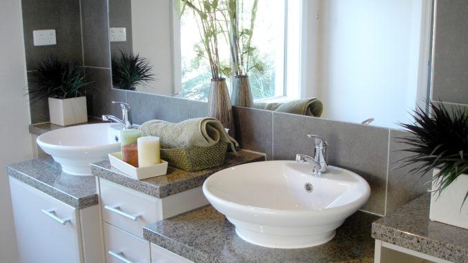 Ein Badezimmer mit zwei Waschbecken und Unterschränken in weiß