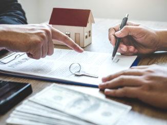 Vertragsunterlagen auf dem Tisch mit Händen darüber
