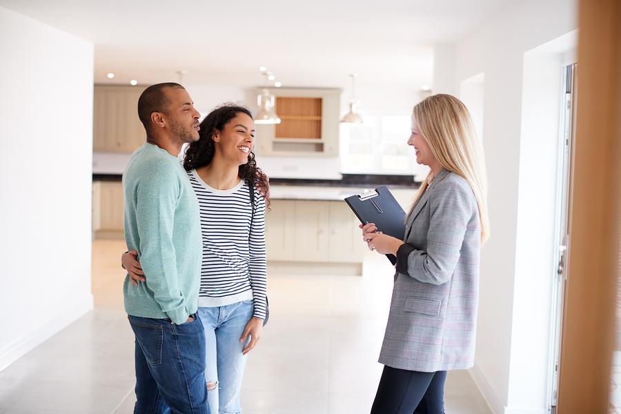 Drei Menschen stehen in einer Immobilie und besprechen sich.