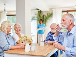 Senioren sitzen zusammen am Tisch und unterhalten sich
