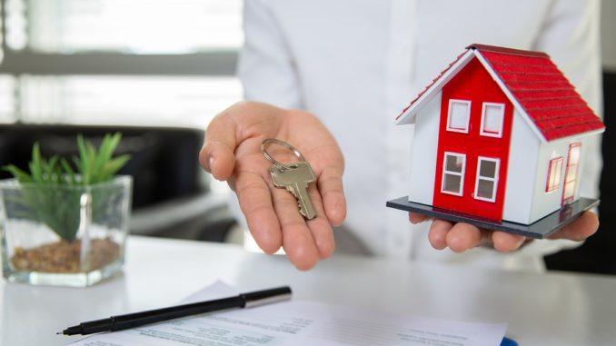 Jemand hält einen Schlüssel und ein Modell-Haus in der Hand