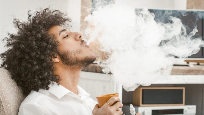 Ein junger Mann mit Afro raucht in der eigenen Wohnung