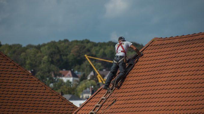 Handwerker ist gesichert auf Dach und arbeitet.
