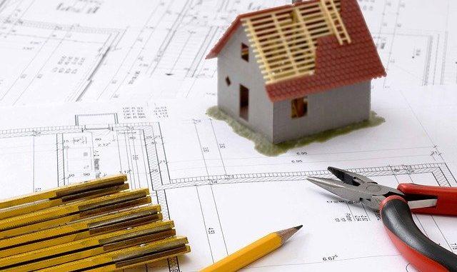Ein Modellhaus steht auf einem Bauplan