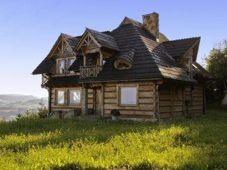 Modernes Holzhaus steht auf Wiese am Berghang