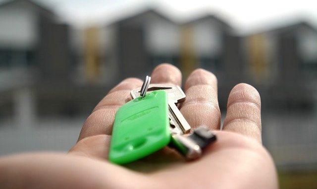 Eine Person hält einen Haustürschlüssel in der Hand