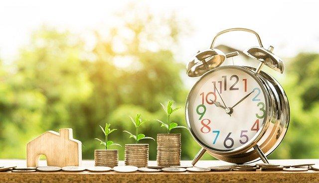 Ein Wecker mit Holzhaus und Geldmünzen