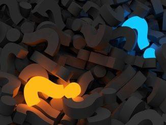 Zwei verschieden farbige Fragezeichen auf schwarzem Hintergrund