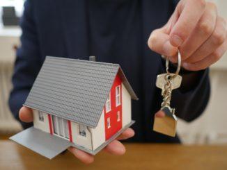 Makler hält Schlüssel und Modellhaus in den Händen